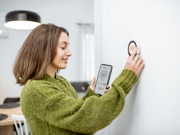 Woman adjusting home thermostat