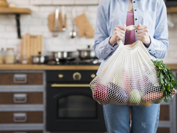 Adult woman holding reusable bag with organic vegetables